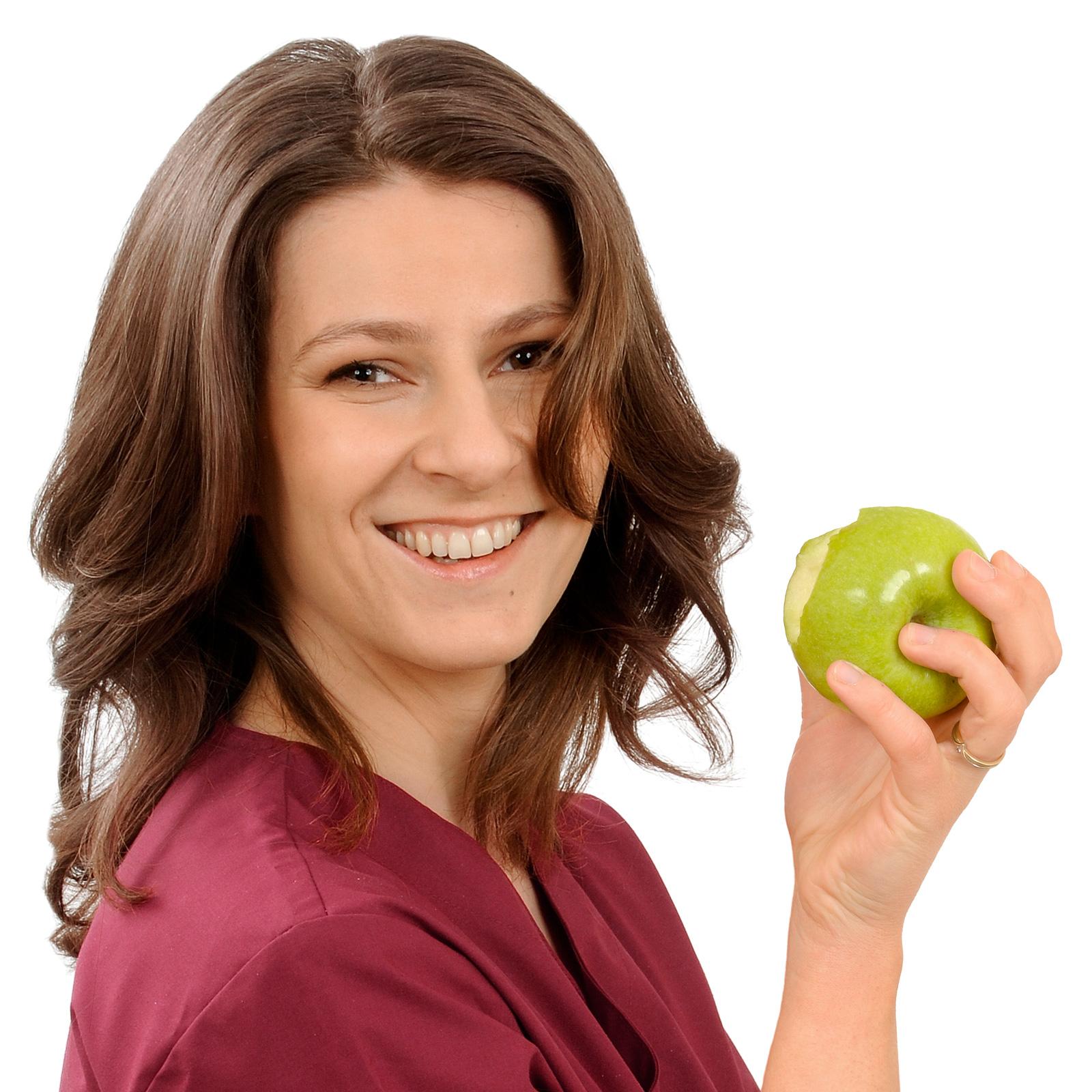 Judith Ehrich hält einen angebissenen Apfel in der Praxis für Zahnmedizin.